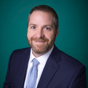 Professional headshot of male wearing suit and tie