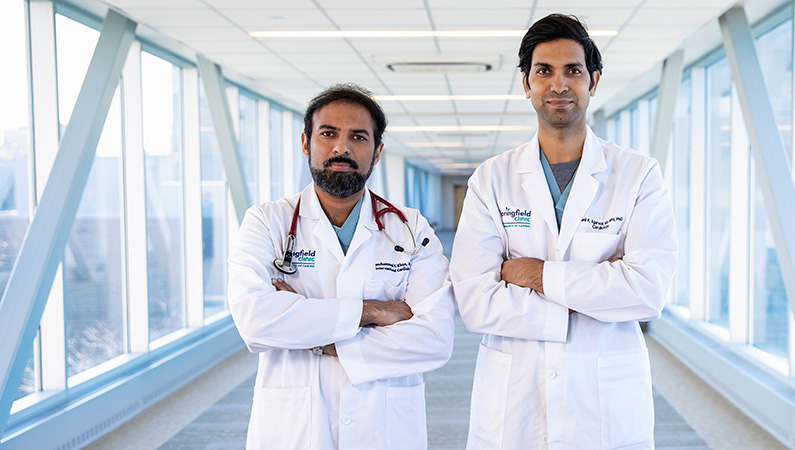 Two male doctors with dark hair standing with their hands crossed in a well-lit walkway