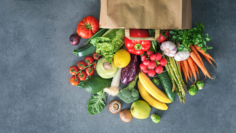 Brown paper bag with fresh fruit and veggies pouring out