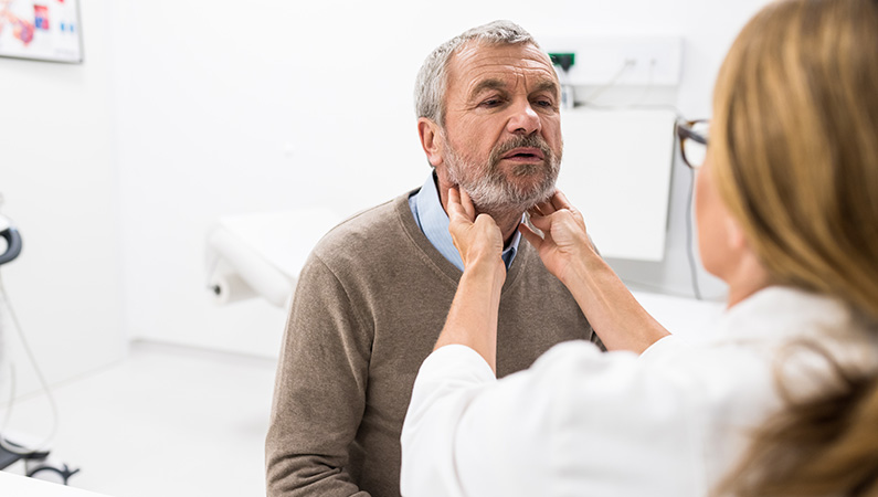 Patient getting throat checked by medical professional in medical office setting