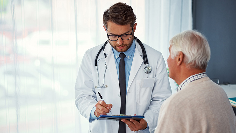 Elderly patient conversing with middle-aged male doctor