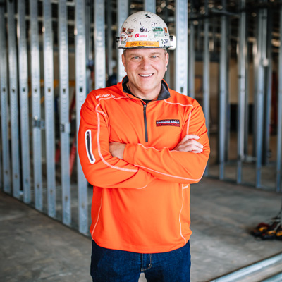 Male wearing bright orange sweatshirt smiling with hard hat on in construction zone