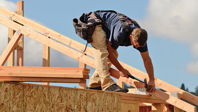 Man constructing structure in outdoor setting