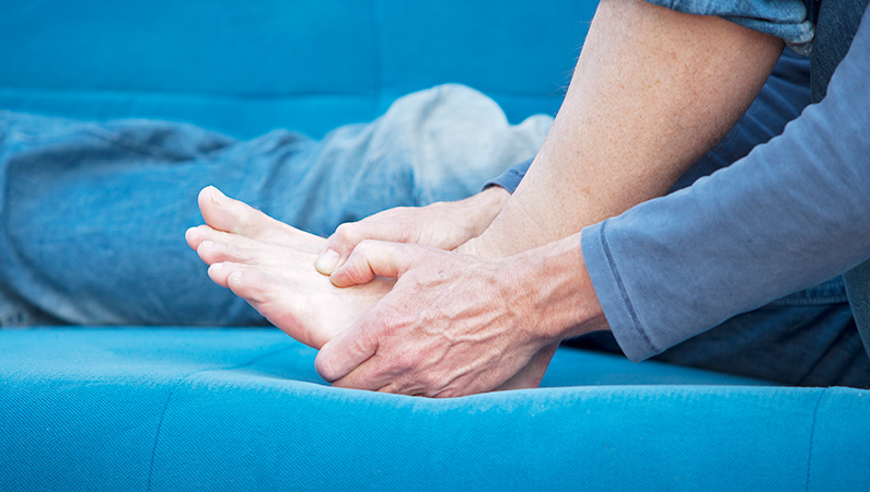 Older male gripping his foot while sitting down on blue couch