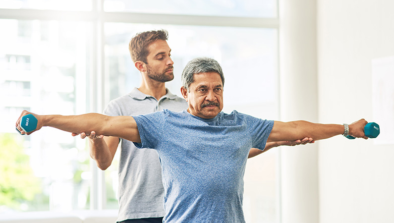 Patient lifting small dumbbell weights with the assistance of young medical professional