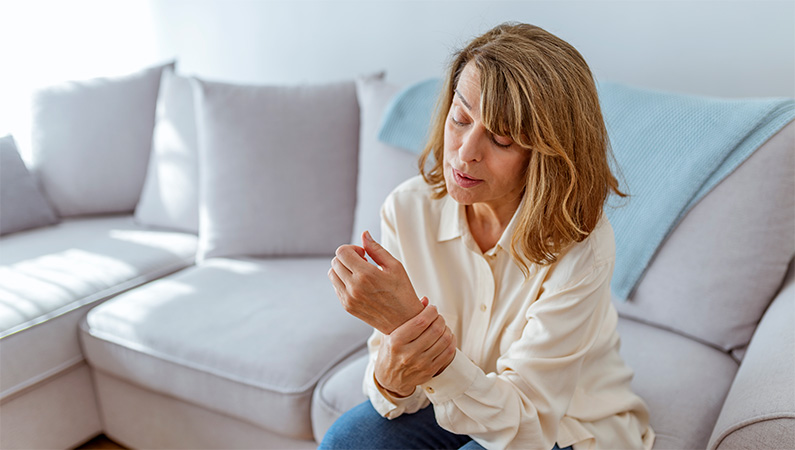 Woman sitting on edge of neutral couch gripping wrist in visible pain
