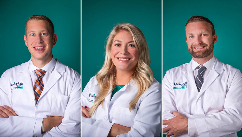 Three medical professionals wearing white medical coats smiling on green background