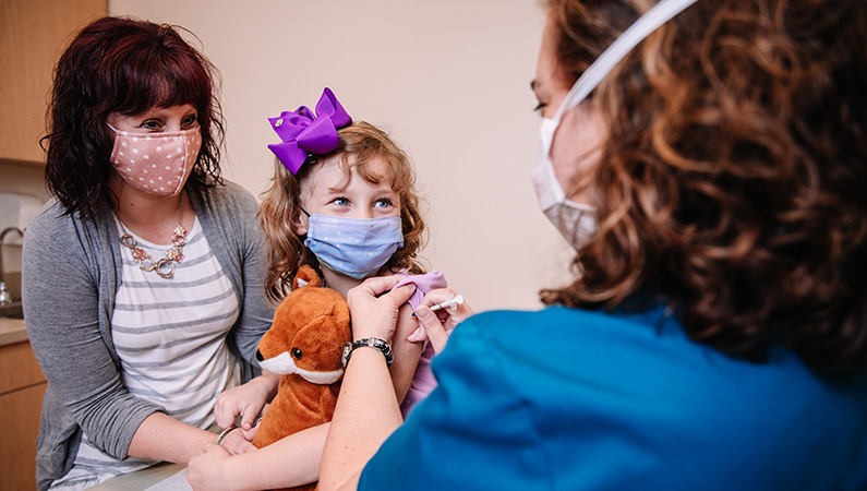 Mom and child patient interacting with medical provider in exam room