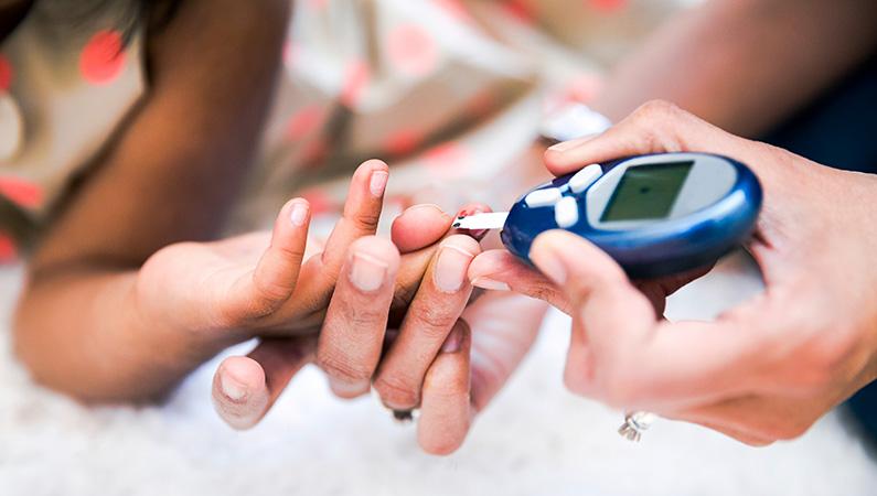Individual checking blood sugar using a blood glucose meter