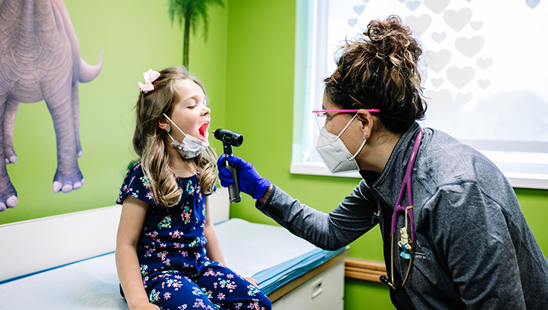 Young female patient in kid-friendly bright exam room getting throat checked by female medical professional