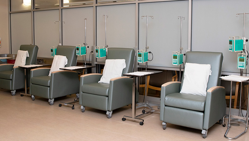 Empty chairs with pillows connected to infusion medical equipment