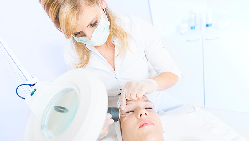 Female in exam room with eyes closed getting cosmetic medical services performed on face