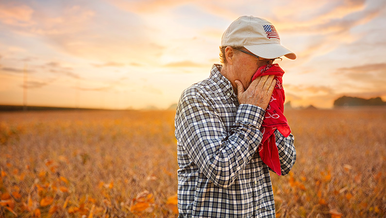 Male wearing hat sneezing into red handkerchief standing in front of freshly harvested field