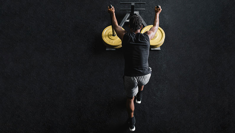 Male in workout clothing pushing weights