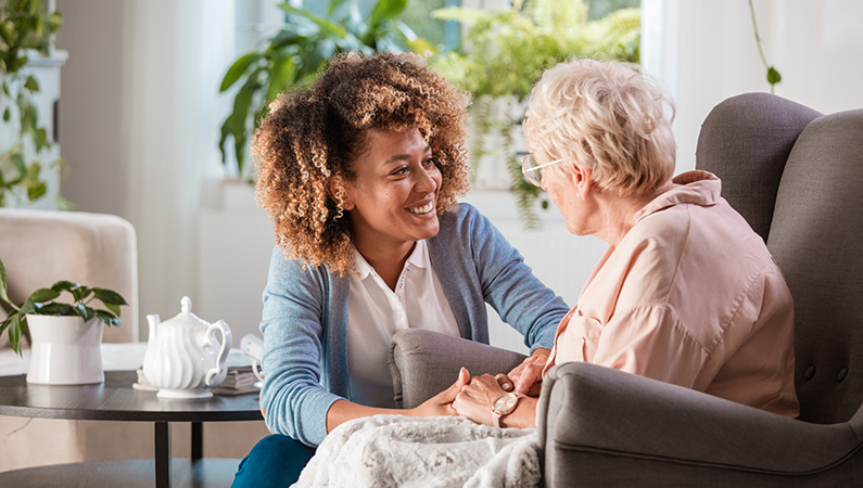 Female with black curly hair sitting down holding hands with an elderly woman in an assisted living setting