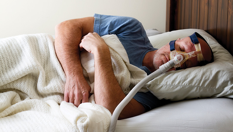 Male sleeping in a bed with the assistance of a CPAP machine.