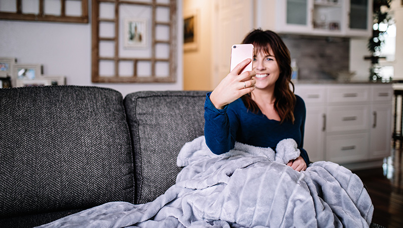 Young female in a home setting sitting on couch with fuzzy blanket looking into smartphone