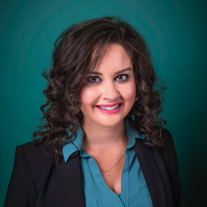 Professional headshot of female with dark curly hair
