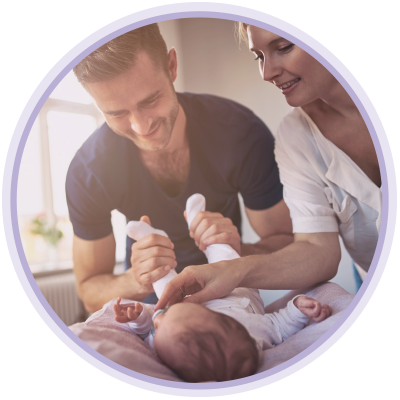 Couple interacting with and entertaining newborn baby