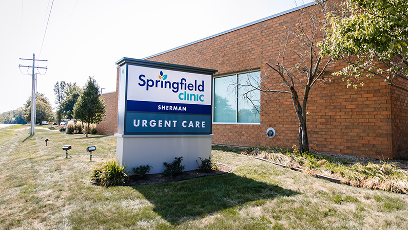Exterior sign in front of single story brick medical urgent care facility in Sherman, Illinois
