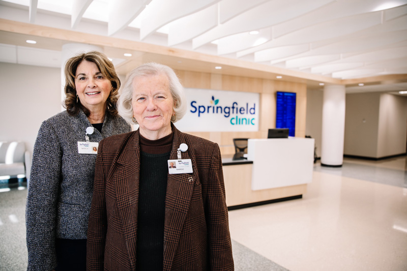 Two female greeters smiling in well-lit lobby