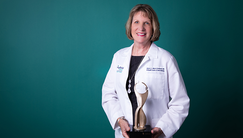 Female medical professional posing with prestigious award