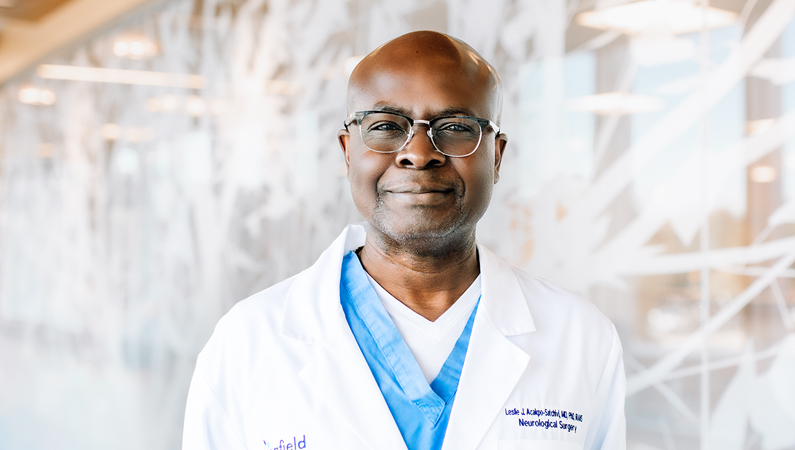 Male wearing glasses and blue scrubs with white medical coat posing in front of wall mural
