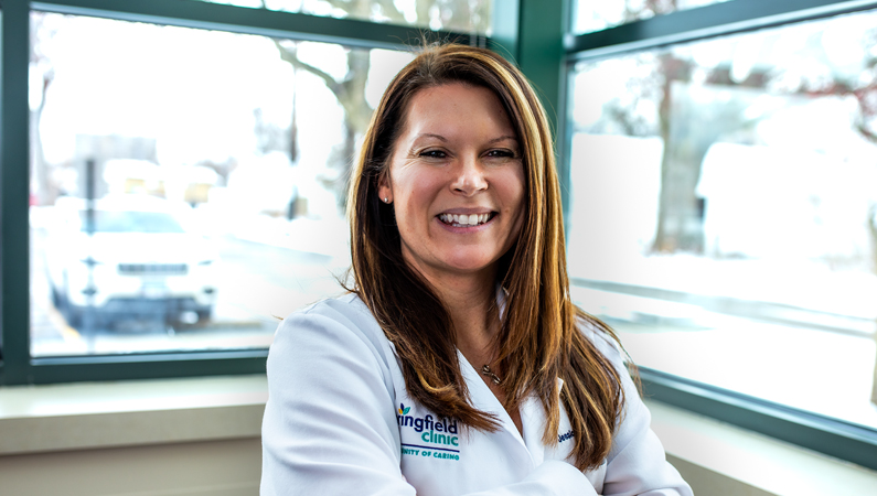 Female with dark straight hair wearing white medical coat smiling in front of windows