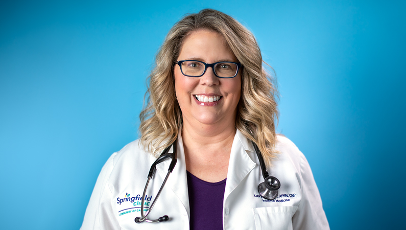 Female with light curly hair wearing glasses and white medical coat smiling in front of bright blue background