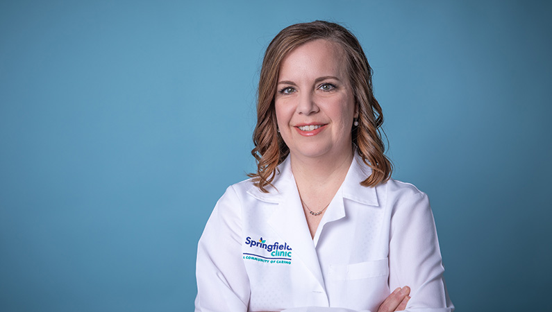 Female with short hair wearing white medical coat smiling in front of studio-lit blue background