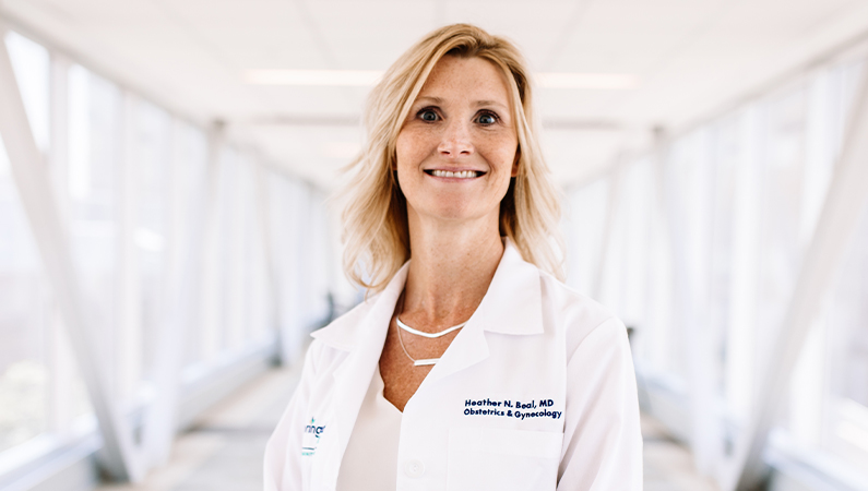 Woman in a white doctors coat smiling in a well lit walkway.