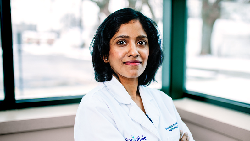 Female with short dark hair wearing white medical coat posing in front of windows