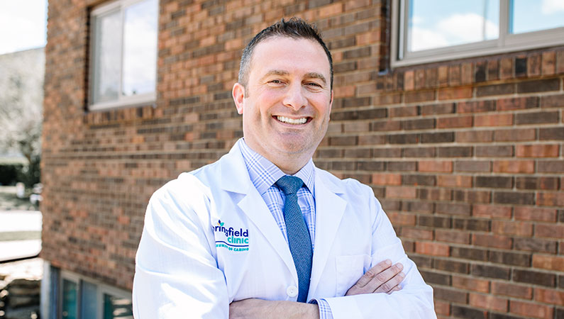 Male gastroenterologist wearing white medical coat and posing outside medial office building in Macomb, Illinois
