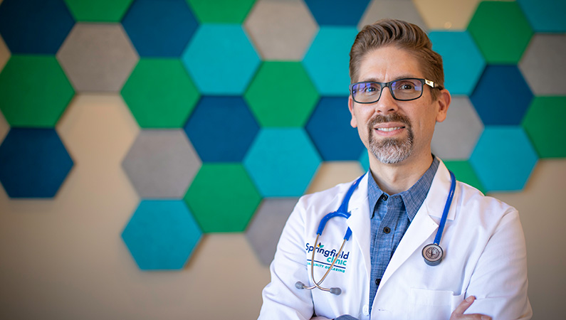 Man in doctors coat smiling in front of a wall with green and blue hexagonal decorations.