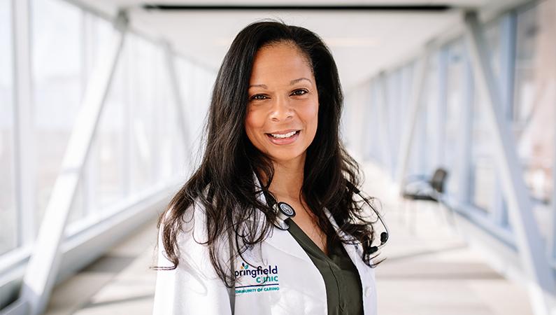 Woman wearing white doctors coat smiling in a well lit walkway