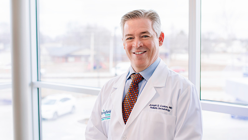 Man wearing a white doctors coat smiling in front of a window