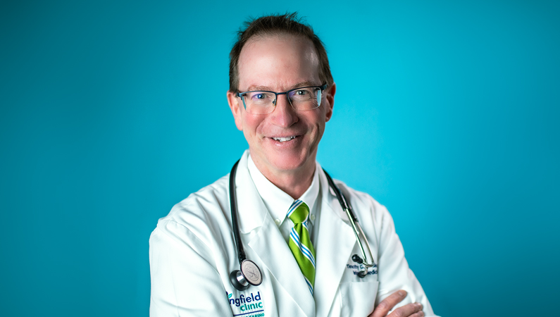 Male wearing glasses and white medical coat with green tie with stethoscope around his neck smiling in front of bright blue background