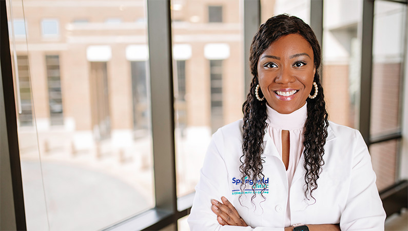 Woman wearing white doctors coat in front of a window.