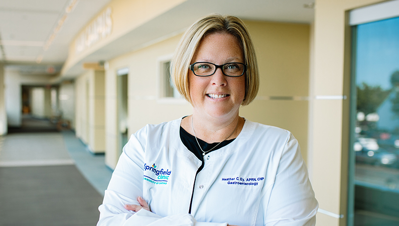 Female with short blonde hair wearing glasses and white medical coat smiling in walkway