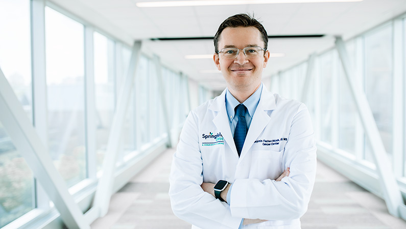 Male wearing glasses and white medical coat posing with arms crossed in well-lit walkway.