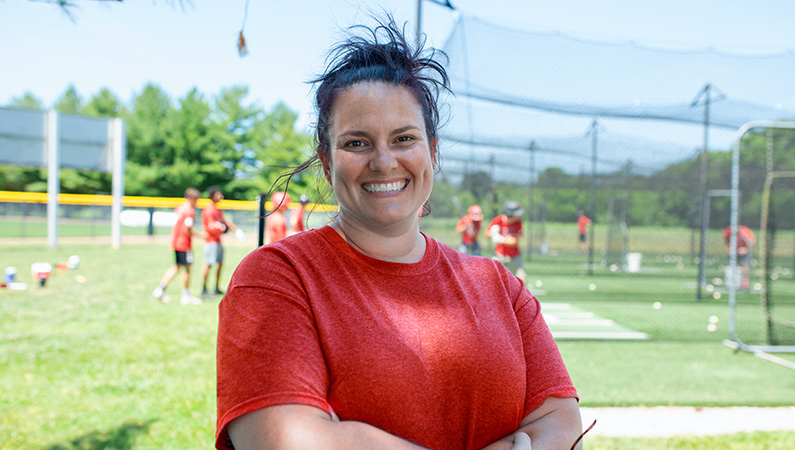 Female with dark hair pulled back wearing red shirt smiling in front of baseball field