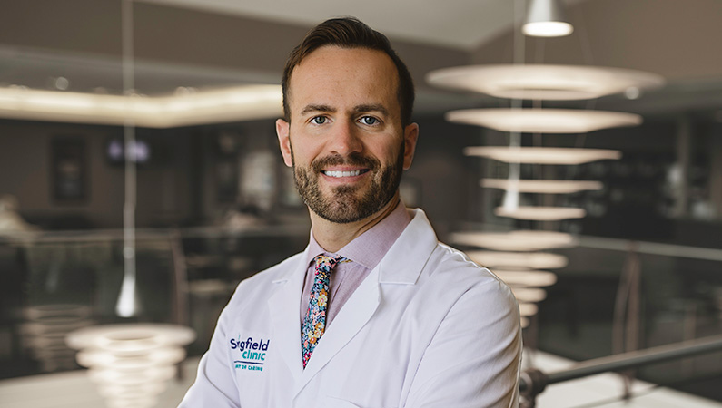 Man wearing a white doctors coat, smiling in a well lit lobby.