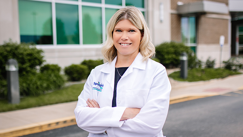 Female with light hair wearing white medical coat smiling in outdoor setting