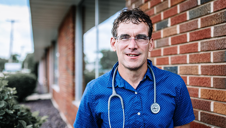 Man wearing a stethoscope around his neck, standing outside of the doctors office building.