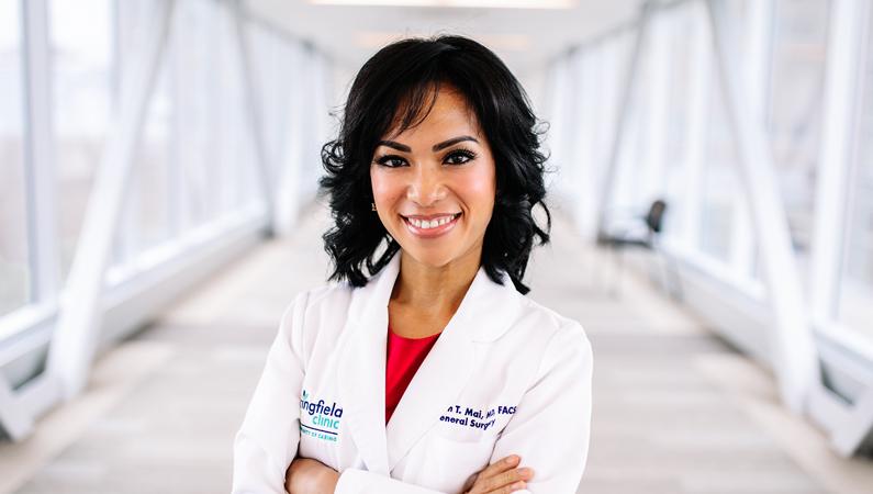 Female with short dark hair wearing white medical coat smiling in well-lit walkway