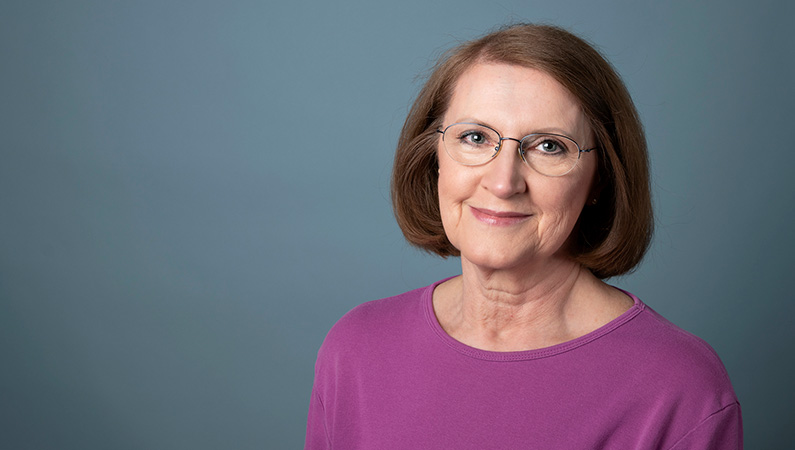 Female with short brown hair and glasses smiling in front of studio lit gray backdrop