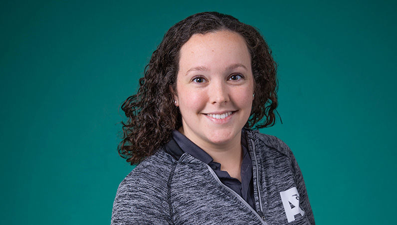 Female with short curly dark hair smiling in front of green background
