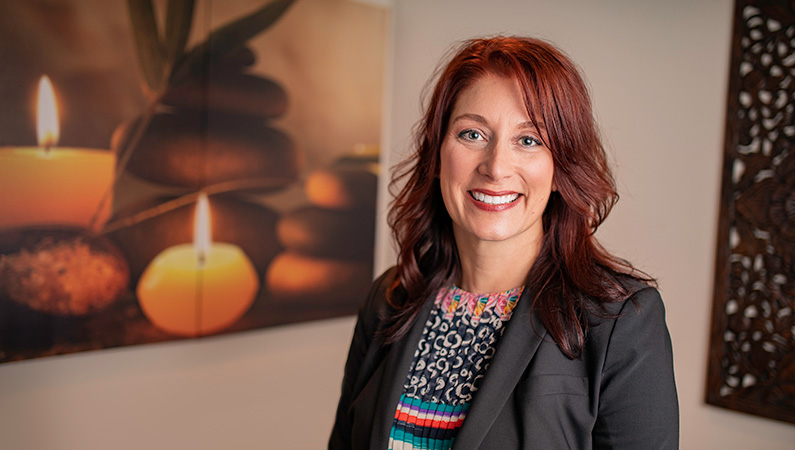 Female with red hair smiling in front of a wall with photos of candles and stones.