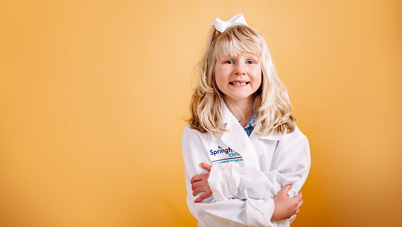 Child with blonde hair in oversized medical white coat crossing arms smiling on bright yellow background