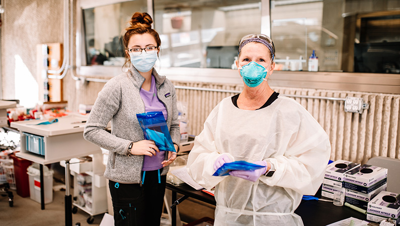 Two lab workers with medical masks on in the drive-up lab office.